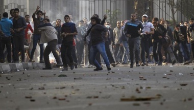Anti-government protesters and members of the Muslim Brotherhood throw stones and glasses during clashes with supporters of Egypt's army and police at Ramsis street, which leads to Tahrir Square in downtown Cairo