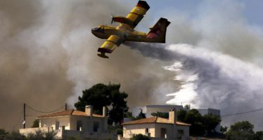 A firefighting plane drops water over a fire near holiday homes in Costa village in the Argolida region, in Southeastern Greece during a developing wild fire, July 20, 2015. Dozens of people were evacuated as firefighters fought the fire, which broke out on Monday afternoon in Panorama in Costa village at a forested area where dozens of summer houses are located, according to local media. REUTERS/Yannis Behrakis