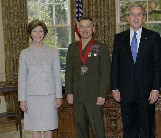 P111005ED-0300dh President George W. Bush and Laura Bush stand with 2005 National Humanities Medal recipient U.S. Marine Matthew Bogdanos, also an Assistant District Attorney in New York, Thursday, Nov. 10, 2005 in the Oval Office at the White House. White House photo by Eric Draper