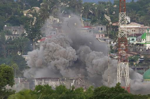 FILE - In this Friday, June 9, 2017 file photo, debris and smoke rises after a Philippine Air Force fighter jets bombed suspected locations of Muslim militants, in Marawi city, southern Philippines. Southeast Asia's jihadis who fought for the Islamic State in Iraq and Syria now have a different battle closer to home in southern Philippines. It's a scenario raising significant alarm in Washington. The recent assault by IS-aligned fighters on the Philippine city of Marawi has left almost 300 people dead, exposing the shortcomings of local security forces and the extremist group's spreading reach. (AP Photo/Aaron Favila, File)